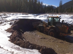 From October 21-22, 2013, crews worked to remove sediment from settling pond on the Fraser River on the east side of U.S. Highway 40 near the entrance of the Mary Jane ski area. (Photo courtesy of Colorado Department of Transportation)