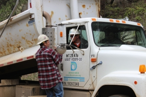 Tony Stengel, assistant foreman of the South Boulder District, talks with Rich Abbott, Gross caretaker, about rebuilding the road leading to Gross headquarters. Caretaker Steve Bauman sits on the driver's side.