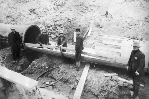 Crews connect a 48-inch wood-stave pipe to a steel pipe crossing Cherry Creek in this 1910 photo. Fifty years ago, the last wood stave pipe was removed from service.