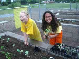 Two happy girls working in raised garden beds at Bradley Garden Club.