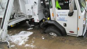 The tires of a new Denver Public Works trash truck became stuck after driving over a temporary road patch that was weakened by a water pipe leak on south Jasmine Street near east Mexico Avenue in southeast Denver.