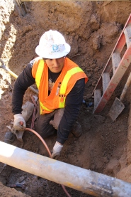 Jose Saldivar, Denver Water  mechanic, connecting a service line to the new 6-inch-diameter water main on south Jasmine Street.