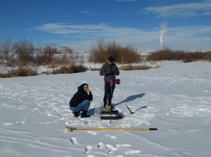 Water quality investigators gather samples all year long. Aubrey Miller (left) and James Berrier, drill through two feet of ice on the Colorado River near Kremlin to gather samples.