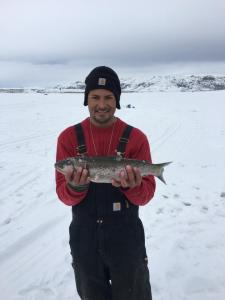 A lucky fisherman pulls in a beautiful rainbow trout during the Williams Fork Ice Fishing Tournament.