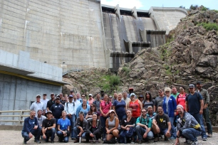 Employees gather in front of the Williams Fork dam after touring the hydroelectric plant.