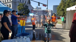 Denver Water employees set up a hose with a nozzle to mist hot fans with water at the NFL Kickoff event in Civic Center Park, which was a hit, especially with kids.